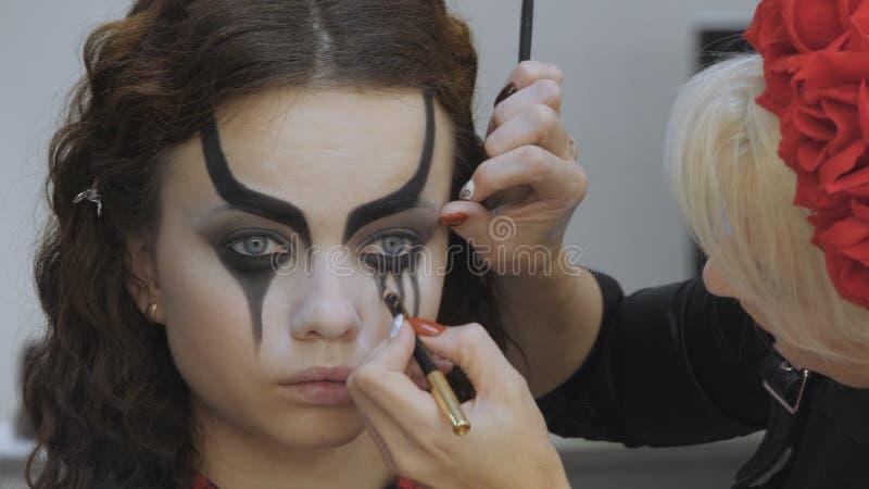 Easy Halloween Makeup Mädchen in einem Schönheitssalon Stilistische Darstellung auf der Vorderseite des Modells Das Werk eines Ma lizenzfreies stockbild
