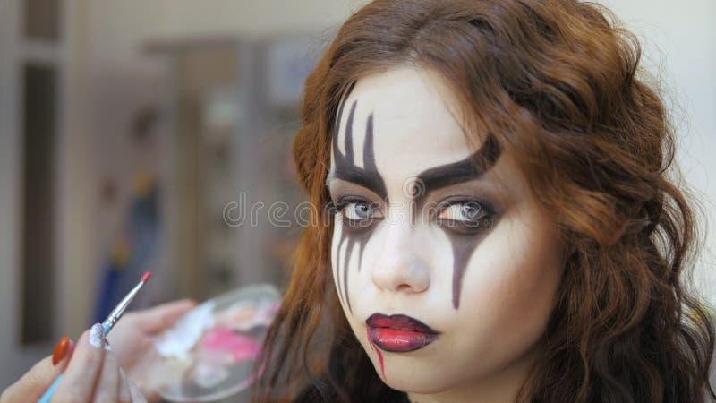 Easy Halloween Makeup Make-up auf das Gesicht Anbringen roter Farbe auf die Lippen lizenzfreies stockbild