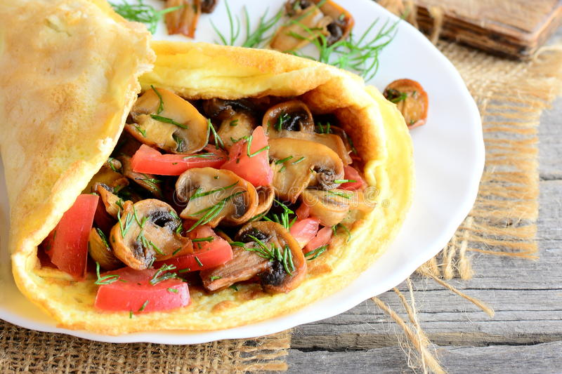 Easy mushrooms omelet recipe. Homemade omelette stuffed with mushrooms, tomatoes and dill on a plate and old wooden background stock photo