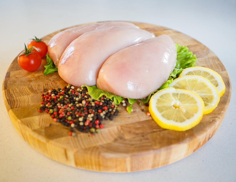 Easy raw Chicken fillet on wooden round board on white background. royalty free stock photo