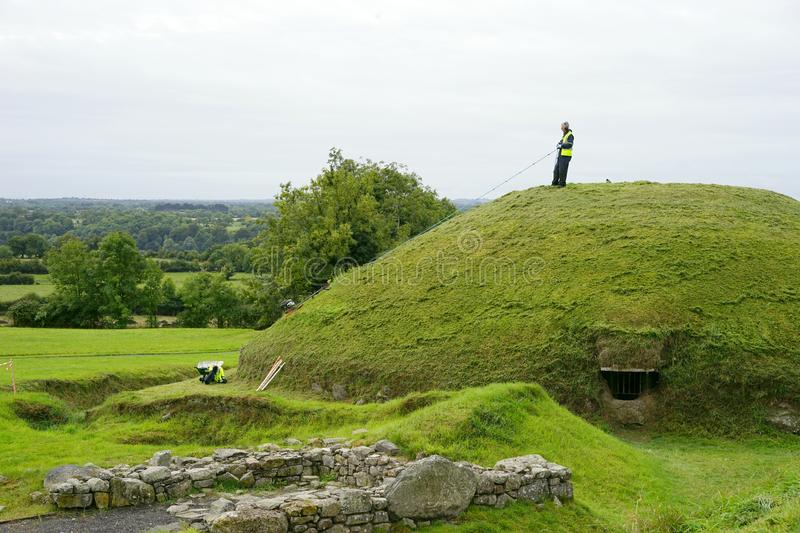 Easy way to mow a neolithic tomb mound. The Boyne Valley Mounds at Newgrange, Knowth and Dowth were built around 3200BC making them older than Stonehenge in royalty free stock images