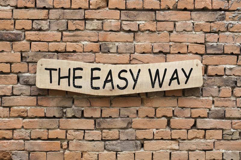 The Easy Way. Written on wooden sign on brick wall background stock photography