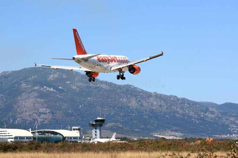 Easyjet A319 almost on the ground. An Easyjet Airbus A319 is almost touching down in Bastia, France. Airport is in the background, as well as the mountains royalty free stock images