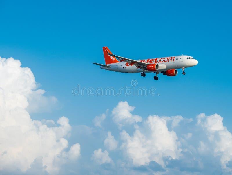 Easyjet Airbus A320 que vuela cerca en las nubes blancas y el cielo azul, aterrizando en el aeropuerto internacional de Larnaca imágenes de archivo libres de regalías