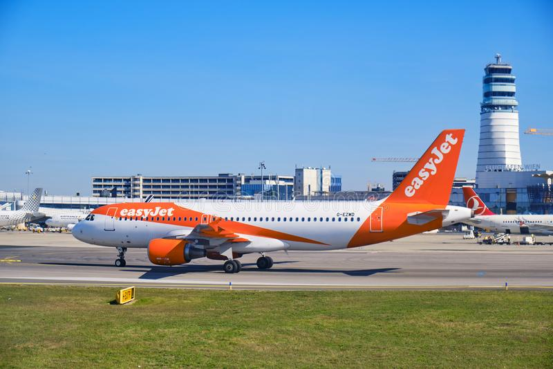 EasyJet aircraft on the Vienna International Airport VIE runway, with control tower in the back and clear blue skies royalty free stock photography