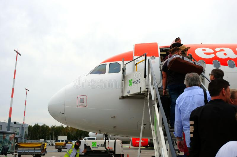 Easyjet boeing boarding and ready for departure at Berlin Shonfeld airport, Germany. Funny ground crew posing to the royalty free stock photo