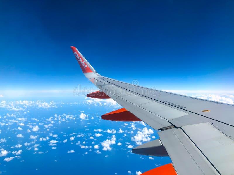 Easyjet-Logo auf Flugzeugflügel des Easyjet-Flugzeugfliegens über t lizenzfreies stockbild