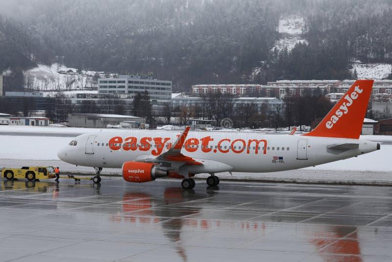 Easyjet som bogseras i den Innsbruck flygplatsen, GÄSTGIVARGÅRD, insnöad vinter fotografering för bildbyråer