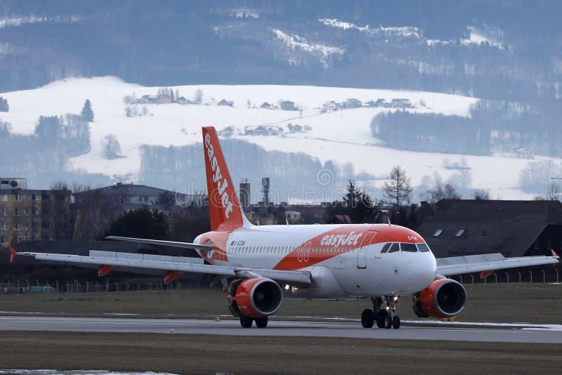 Easyjet a tributar no aeroporto de Salzburg, neve nas montanhas imagem de stock royalty free