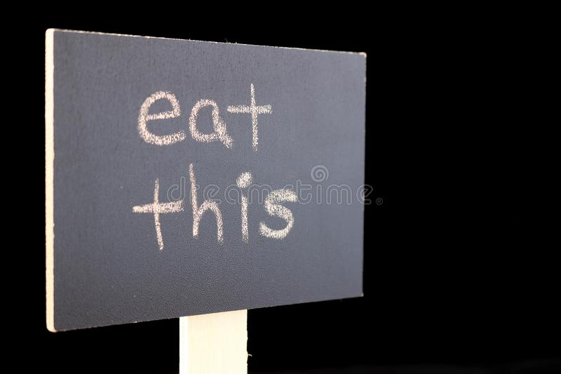 Eat this - chalkboard sign on a black background. Chalkboard or blackboard sign with `eat this` text - good for social media posts, blogs, internet publishing stock photos