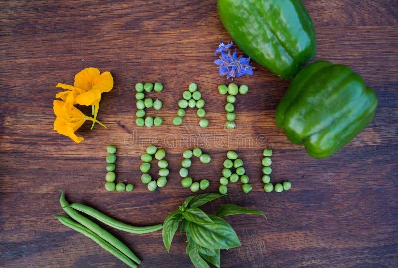 """""""Eat de uitdrukking van Local† van groene erwten op houten achtergrond wordt gemaakt die stock afbeelding"""