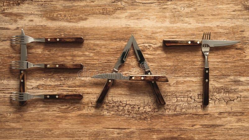 Eat escrita con las bifurcaciones y los cubiertos de los cuchillos en la tabla de madera rústica fotos de archivo libres de regalías