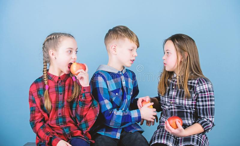 Eat fruit and be healthy. Promoting healthy nutrition. Boy and girls friends eat apple. Teens with healthy snack. Group stock images