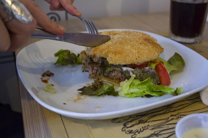 Eat a hamburger with fork and knife.  royalty free stock images