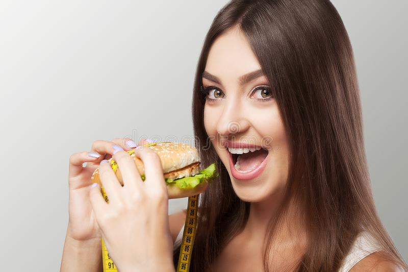 Eat hamburger A young girl with appetite eats a hamburger. Diet. Harmful food. The concept of health and beauty. On a gray background stock photo