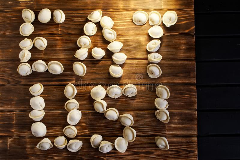 Eat me. Letters from dumplings on dark boards. Country style. royalty free stock photos