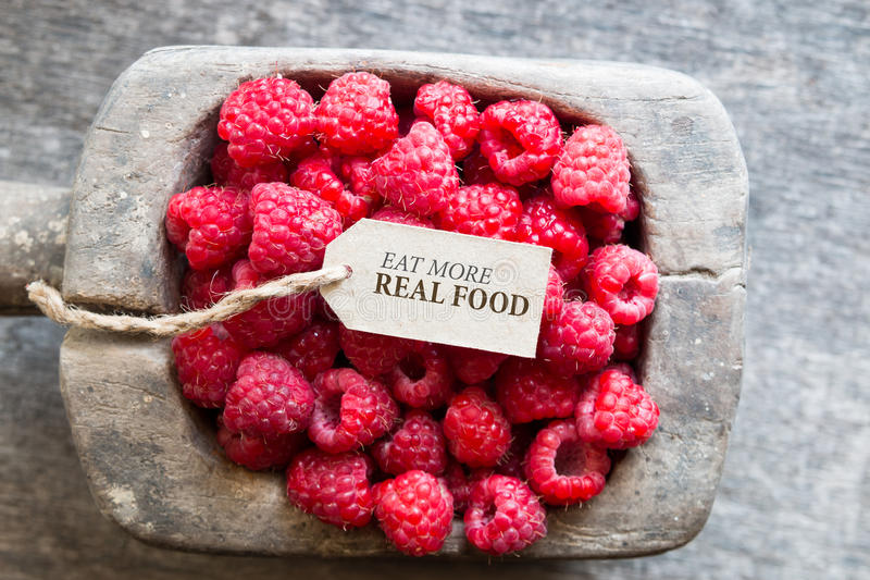 Eat more real food. Raspberries and a tag with the inscription royalty free stock photography