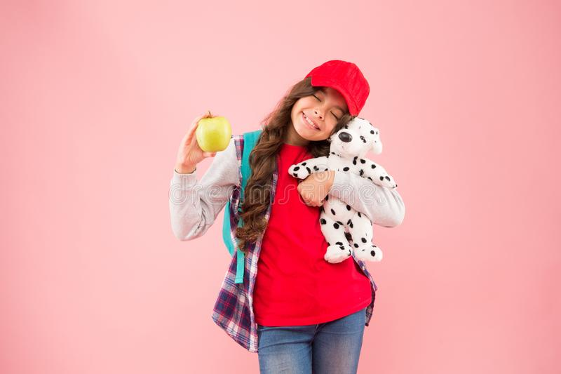 Eat organic. Happy small child hold toy and organic apple fruit on pink background. Healthy little girl choose natural stock images