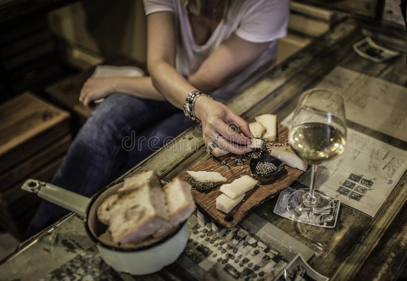 Afternoon with friends while having an aperitif and drinking a glass of wine in the restaurant. Eat salami and cheese and drink white wine in Milan during the royalty free stock images