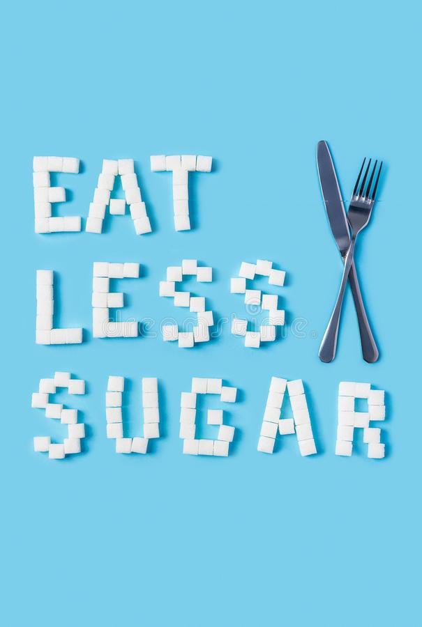 Eat less sugar inscription made of sugar cubes on trendy blue background stock images