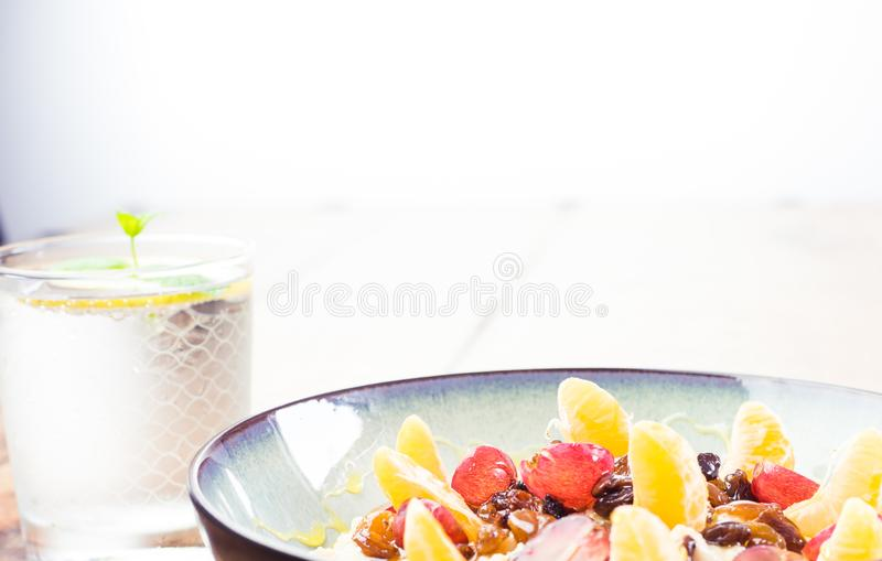 Eat well - healthy and nutritious breakfast oatmeal, fruit, honey, water royalty free stock photos