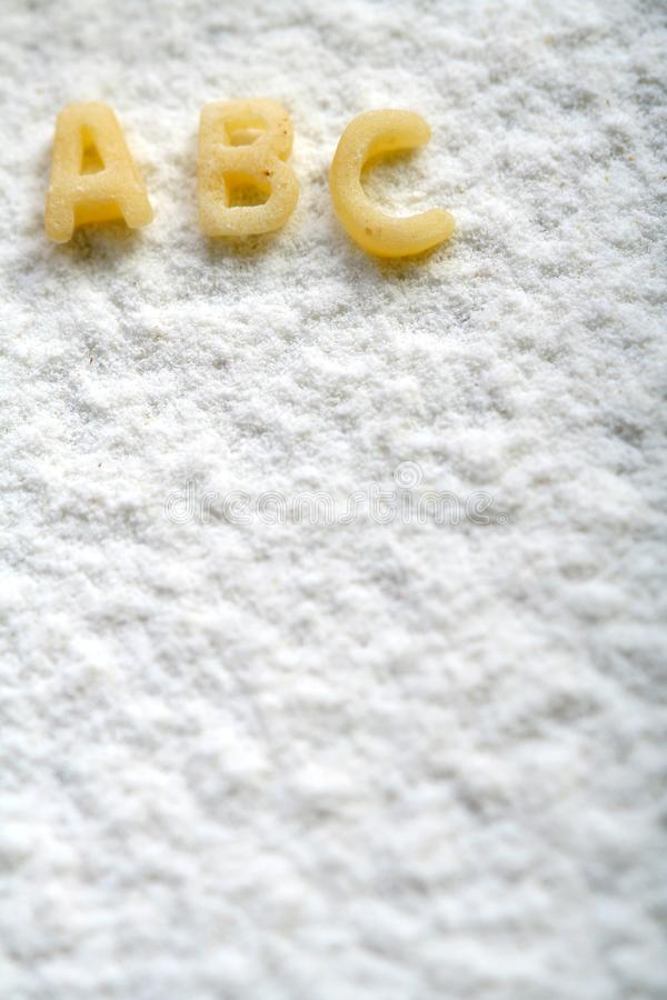 Eatable alphabet on flour, education royalty free stock photo
