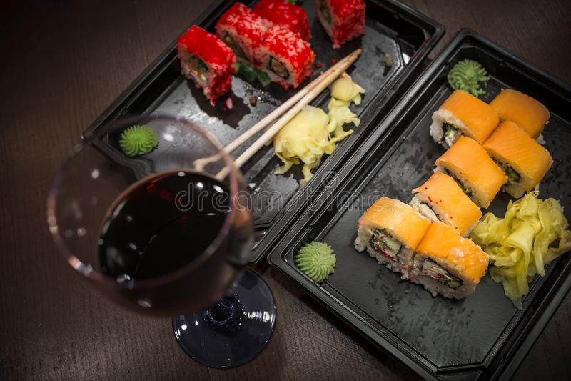 Almost eaten Japanese rolls, packed in plastic containers for the transport of fast food and a glass of red wine. Focus on meal royalty free stock image
