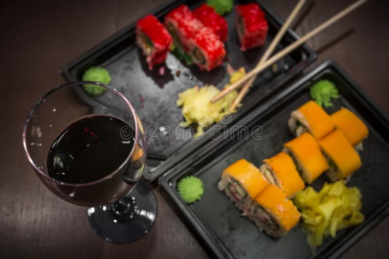 Almost eaten Japanese rolls, packed in plastic containers for the transport of fast food and a glass of red wine. Focus on wine royalty free stock images