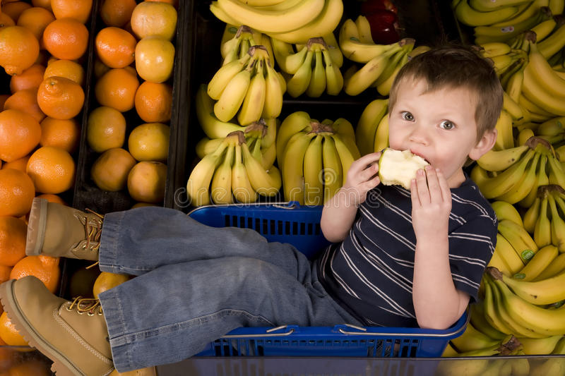 Eating apple banana. A little boy eating a delicious apple while surrounded by bananas royalty free stock photography