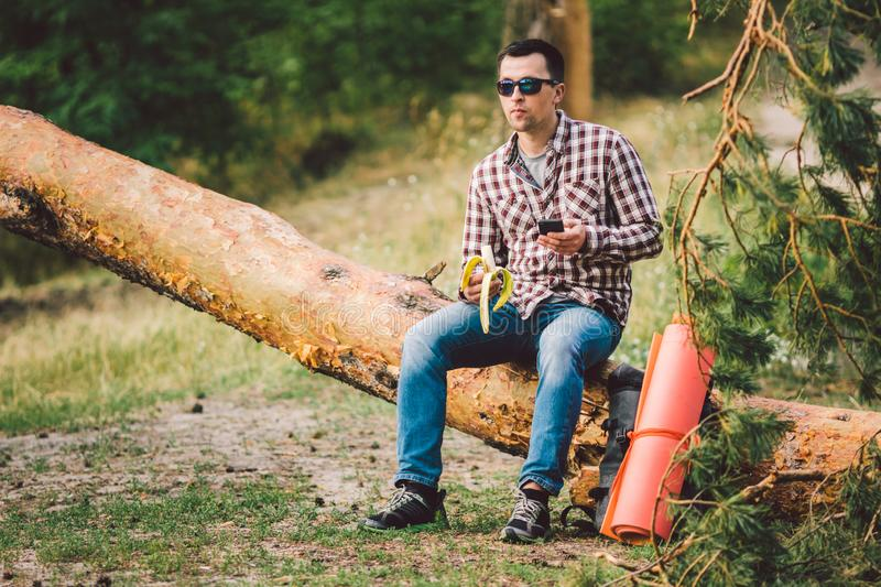 Eating banana Outdoors Hiking Trail. theme hiking and nature travel. Tourist take a rest and eating babanas. picnic in. The forest. tourist eat snack food royalty free stock image