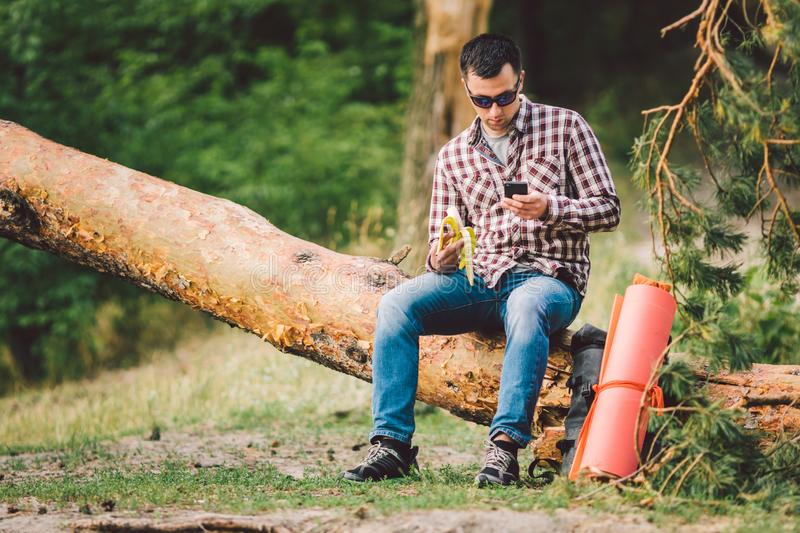 Eating banana Outdoors Hiking Trail. theme hiking and nature travel. Tourist take a rest and eating babanas. picnic in. The forest. tourist eat snack food royalty free stock photo
