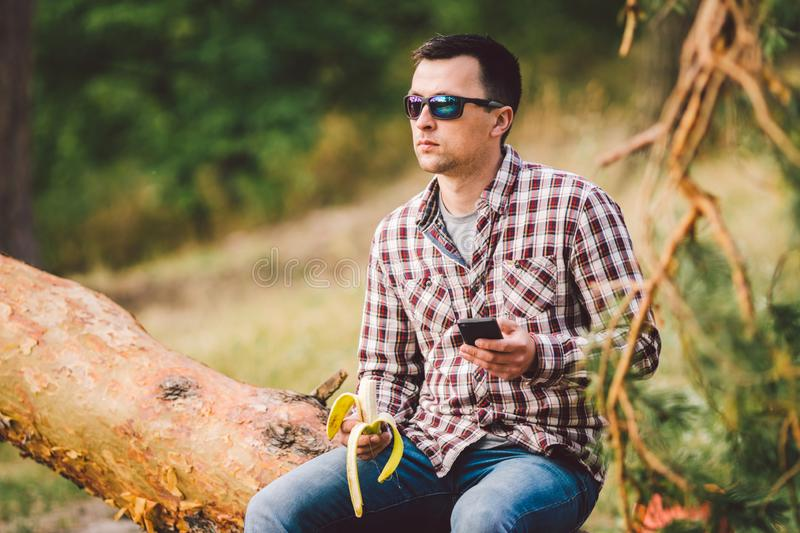 Eating banana Outdoors Hiking Trail. theme hiking and nature travel. Tourist take a rest and eating babanas. picnic in the forest. Tourist eat snack food royalty free stock image