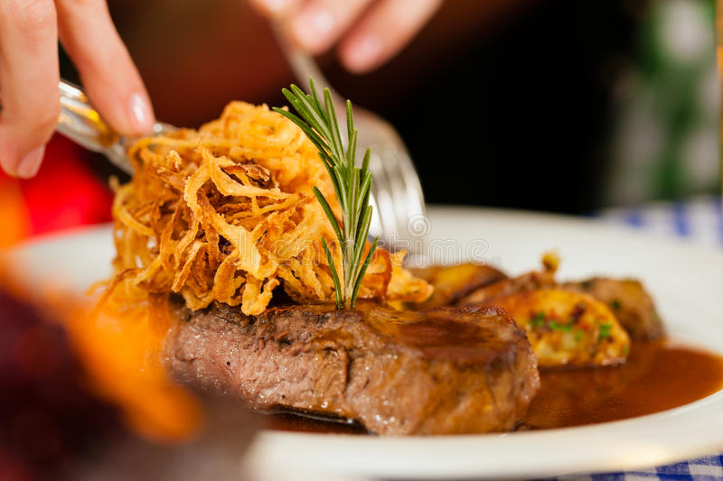 Eating in Bavarian restaurant or pub. Someone eating beef roast in Bavarian restaurant or pub for lunch or dinner royalty free stock images
