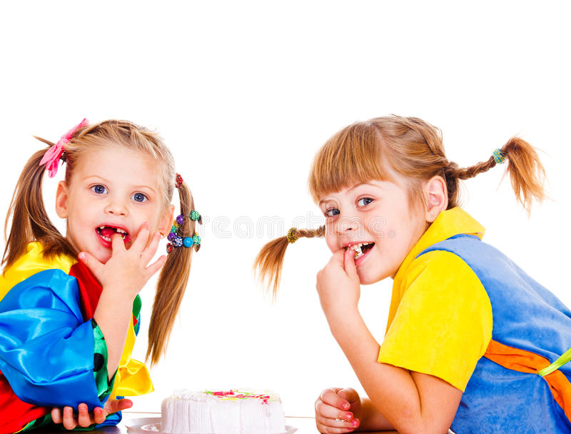 Eating birthday cake. Two sweet girls in bright clothing eating birthday cake royalty free stock image