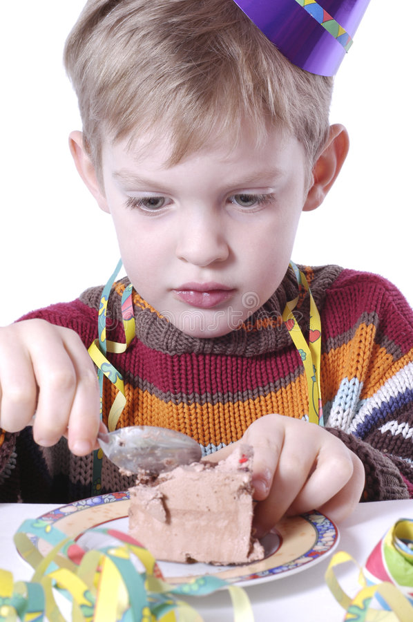 Eating the birthday cake. Boy is eating a piece of his birthday cake royalty free stock photos