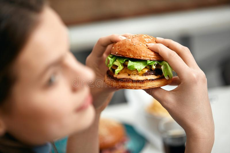 Eating Burger. Woman Holding Hamburger In Hands. At Fast Food Restaurant. High Resolution royalty free stock photography
