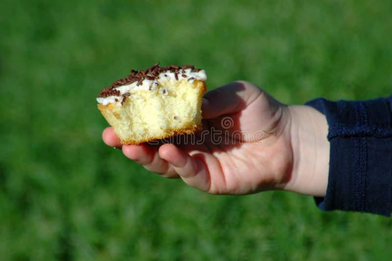 Eating cake. A white little hand of a caucasian child holding and eating a delicious sweet cupcake on a party in the sunshine outdoors royalty free stock photography