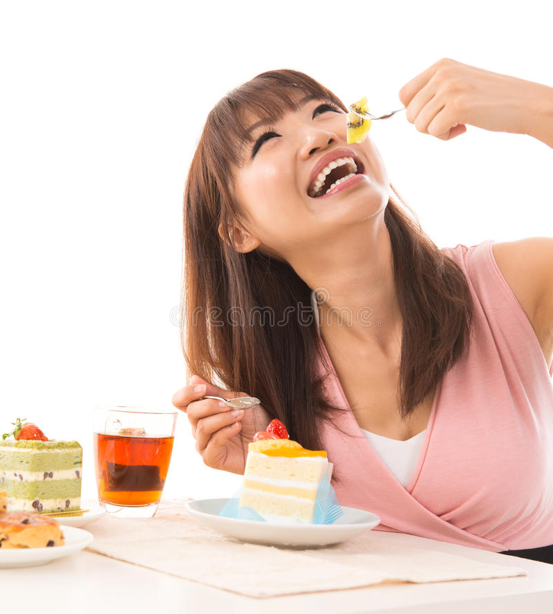 Eating cakes. Smiling Asian woman eating cakes in the living room in her house royalty free stock image