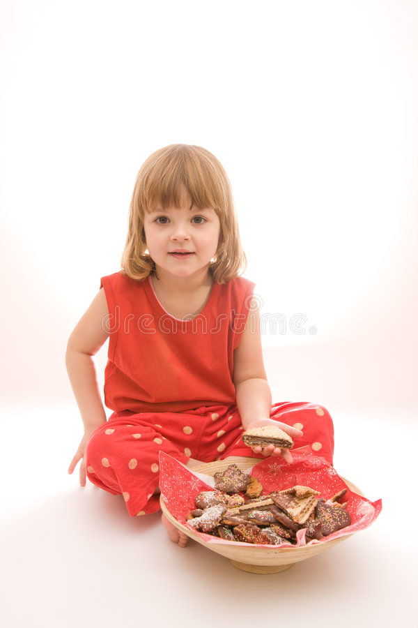 Eating cakes. Little, cute girl eating cakes isolated on white stock images
