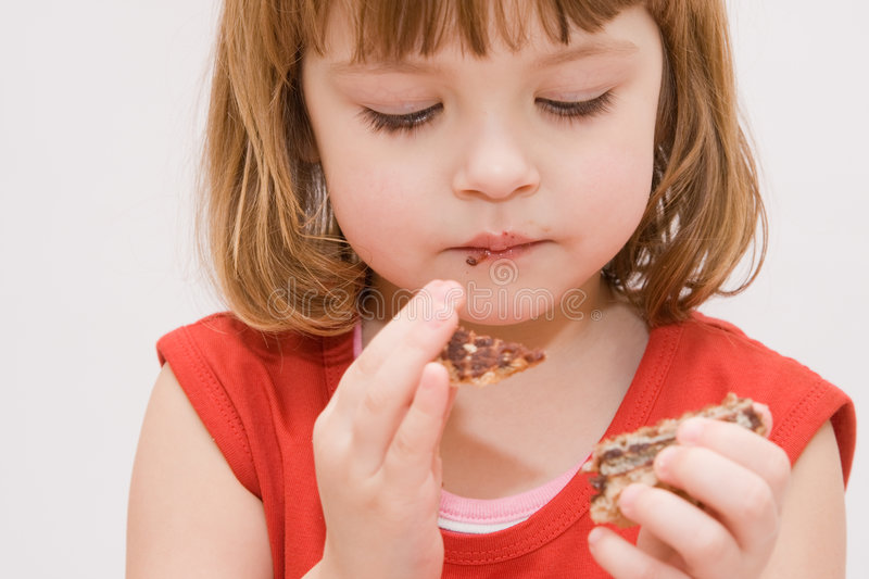 Eating cakes. Little, cute girl eating cakes isolated on white stock photos