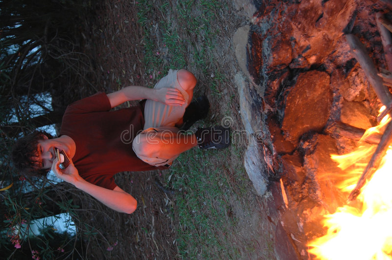 Eating campfire smores. A teen eating a smore by a campfire royalty free stock photography