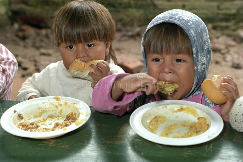 Eating children during food distribution. ARGENTINA, Jujuy Province, village Colonia Santa Rosa: group portrait of Indian children, boys, who have no eye for the royalty free stock photos