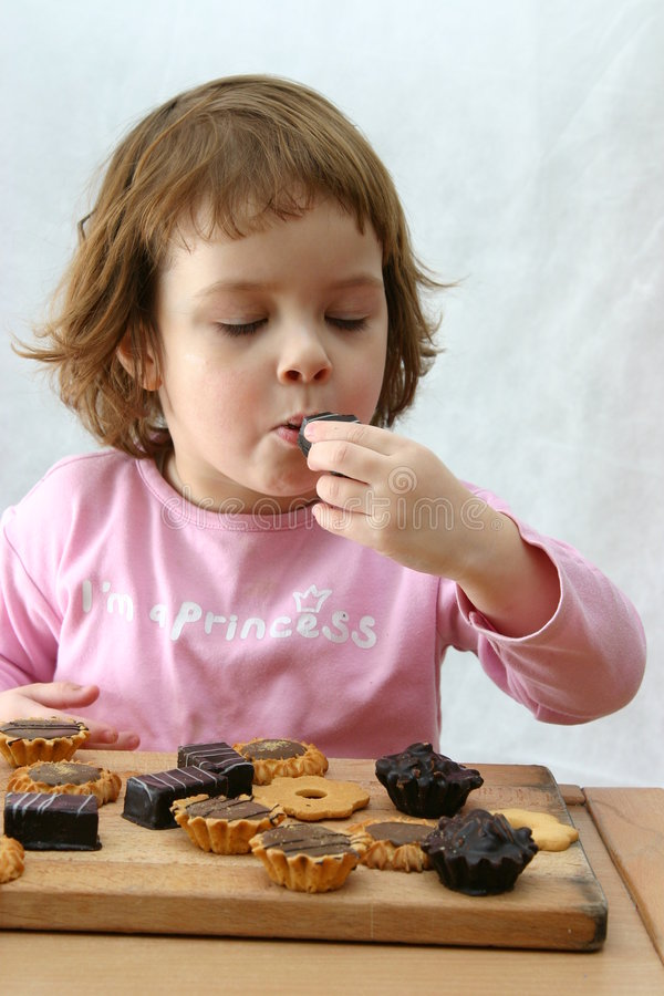 Eating chocolate cakes. Cute child eating tasty chocolate cookies on white stock photos