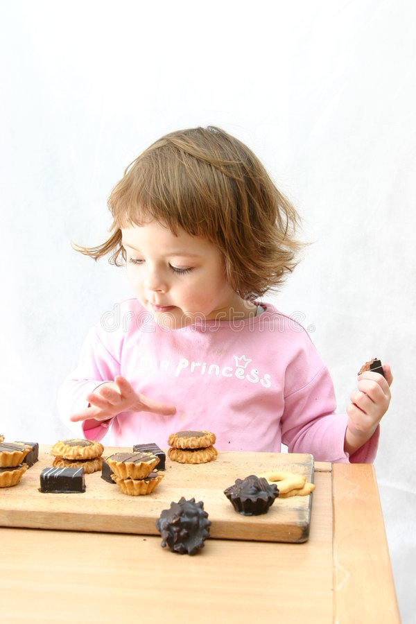 Eating chocolate cakes. Cute child eating tasty chocolate cookies on white royalty free stock photos