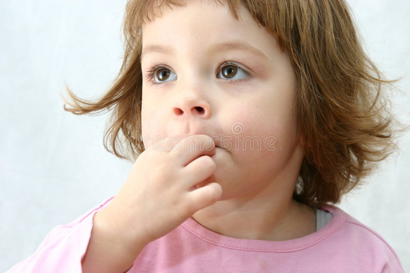 Eating chocolate cakes. Cute child eating tasty chocolate cookies on white stock photo