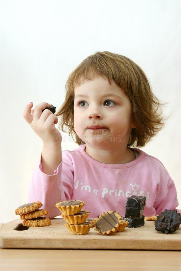 Eating chocolate cakes royalty free stock photo