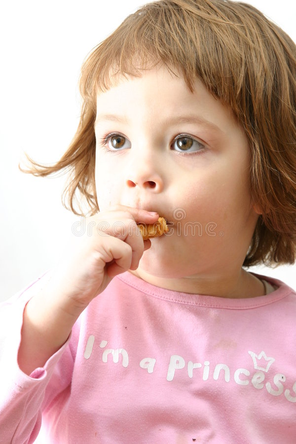Eating chocolate cakes. Cute child eating tasty chocolate cookies on white royalty free stock photography