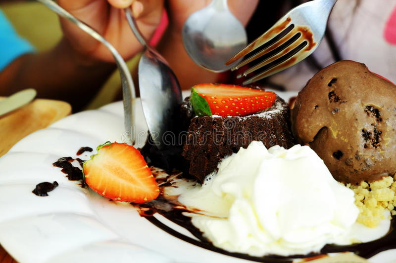 Eating chocolate Ice Cream and baked bread stuffed with chocolate and a strawberry on top. royalty free stock image
