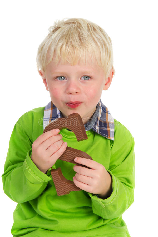 Eating a chocolate letter. Little child is eating a Sinterklaas chocolate letter stock image