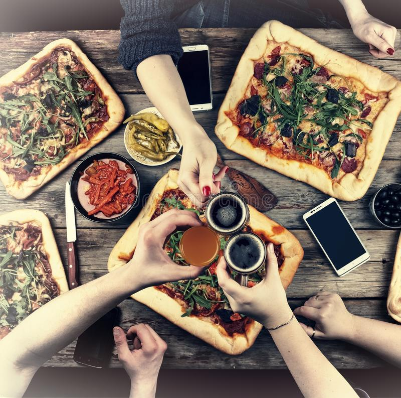 Eating Concept. Enjoying dinner with friends, Top view of group of people having dinner together while sitting at the rustic woode stock photography